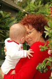 A grandmother in striking red with her grandbaby Stock Photography