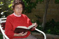 Grandmother Studies Bible in G. A kind looking elderly woman sits in her backyard studying her Bible Stock Photos