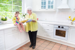 Grandmother and sweet girl baking pie in white kitchen. Happy beautiful great grandmother and her adorable granddaughter, curly toddler girl in colorful dress Stock Photo