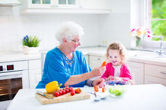 Grandmother and sweet girl making salad Royalty Free Stock Photos