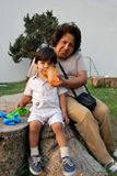 A grandmother taking care of her grandson. She is giving him water Royalty Free Stock Images