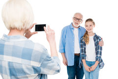 Grandmother taking photo of grandfather and grandchild Stock Photo
