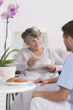 Grandmother talking with caregiver. During tea time Royalty Free Stock Photography