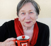 Grandmother with a tea cup. The smiling grandmother with a tea cup Royalty Free Stock Photo