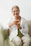 Grandmother with tea. Happy senior female with glass of tea looking at camera Stock Image