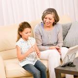 Grandmother teach young girl play flute happy. Grandmother teach young girl to play flute happy sitting on sofa Stock Photos