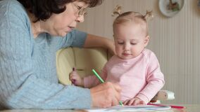 Grandmother teaches granddaughter to draw, selective focus, close up