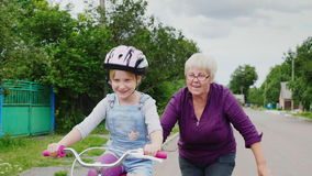 Grandmother teaches her granddaughter how to ride a bicycle. The first successes of children, activity in old age stock footage