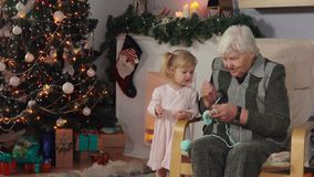 Grandmother teaches to knit her granddaughter stock footage