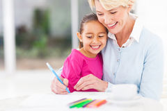 Grandmother teaching granddaughter. Happy senior grandmother teaching her granddaughter how to draw at home stock photos