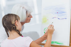 Grandmother teaching granddaughter how to paint Royalty Free Stock Photos