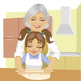 Grandmother teaching granddaughter how to roll out dough to cook pizza in kitchen Stock Photos