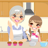 Grandmother Teaching Granddaughter in Kitchen. Grandmother teaching cooking to granddaughter decorating cupcakes together happily in kitchen Royalty Free Stock Image