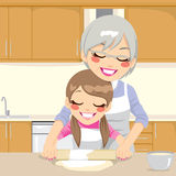 Grandmother Teaching Granddaughter Make Pizza. Grandmother teaching Granddaughter how to make pizza dough together in kitchen Royalty Free Stock Photo