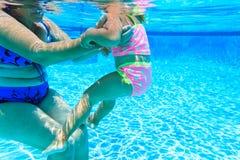 Grandmother teaching granddaughter to swim Royalty Free Stock Images