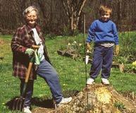 Grandmother teaching grandson lawn work royalty free stock image