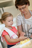 Grandmother teaching her granddaughter baking cookies Stock Photography
