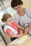Grandmother teaching her granddaughter how to bake cookies Royalty Free Stock Photography
