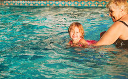 Grandmother teaching little granddaughter to swim royalty free stock photos
