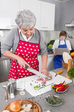 Grandmother teaching young boy to cook meat - family life at hom Stock Photo