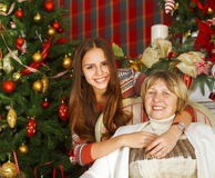 Grandmother and teen granddaughter near the Christmas tree Stock Image