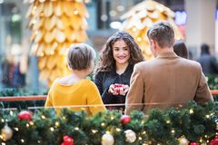 Grandmother and teenage grandchildren in shopping center at Christmas. Royalty Free Stock Image