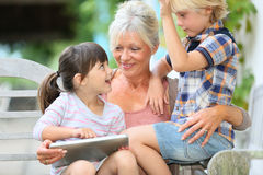Grandmother telling book ytpry to her grandkids. Grandmother with kids playing games on tablet Royalty Free Stock Image