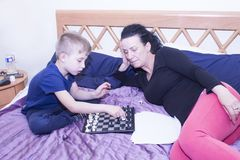 Grandmother trains your grandson to play chess. stock photos