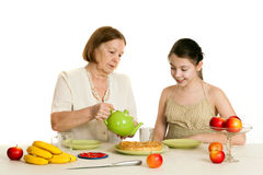 The grandmother treats the granddaughter with tea and pie. At a table Royalty Free Stock Photos