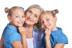 Grandmother with two adorable twin granddaughters. Posing isolated on white background stock photography