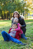 Grandmother with two grandchildren sitting on green grass in autumn park Royalty Free Stock Images