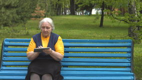 Grandmother uses a tablet computer. An elderly woman sits on a bench in the park and enjoys a tablet PC stock video footage