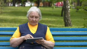 Grandmother uses a tablet computer. 2 Shots. 1. An elderly woman sits on a bench in the park and enjoys a tablet PC stock video footage