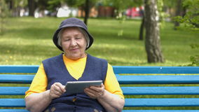 Grandmother uses a tablet computer. 2 Shots. 1. An elderly woman sits on a bench in the park and enjoys a tablet PC stock video