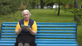 Grandmother uses a tablet computer. 2 Shots. Slow motion. 1. An elderly woman sits on a bench in the park and enjoys a tablet PC stock video footage