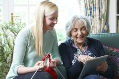 Grandmother Using Digital Tablet As Granddaughter Knits. Smiling Grandmother Using Digital Tablet As Granddaughter Knits Royalty Free Stock Images