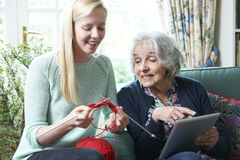 Grandmother Using Digital Tablet Whilst Granddaughter Knits Royalty Free Stock Images