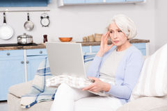 Grandmother using laptop computer. Elderly woman using her laptop computer from home. Mature woman sitting at home and thinking about business and money Royalty Free Stock Photography