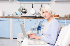 Grandmother using laptop computer. Grandmother writing letter to her family using email. Pretty grandmother using laptop computer at home Royalty Free Stock Image