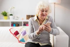 Grandmother using mobile phone. Grandmother using new mobile phone Stock Image