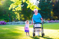 Grandmother with walker and little girl in a park Royalty Free Stock Photo