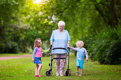 Grandmother with walker playing with two kids. Happy senior lady with a walker holding hands of little boy and girl. Grandmother with grand children enjoy a walk Royalty Free Stock Image