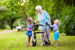 Grandmother with walker playing with two kids. Happy senior lady with a walker holding hands of little boy and girl. Grandmother with grand children enjoy a walk Stock Image