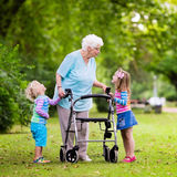Grandmother with walker playing with two kids Royalty Free Stock Image