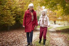 Grandmother Walking Along Autumn Path With Granddaughter Stock Images
