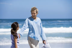 Grandmother walking with granddaughter (7-9) on beach near water's edge, smiling Royalty Free Stock Photography