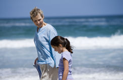 Grandmother walking with granddaughter (7-9) on beach near water's edge, smiling, side view Royalty Free Stock Image