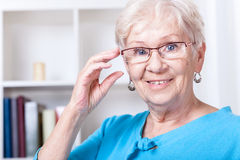 Grandmother wearing reading glasses. Smiling grandmother wearing reading glasses at home royalty free stock photography