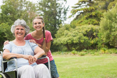 Grandmother in wheelchair and granddaughter smiling into the cam Stock Photo