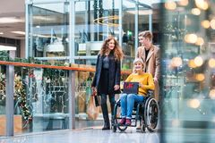 A grandmother in wheelchair and teenage grandchildren in shopping center at Christmas. A senior grandmother in wheelchair and teenage grandchildren with paper stock photos